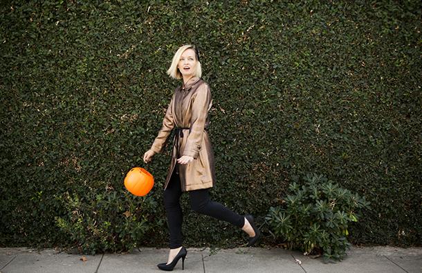 Model wearing halloween fashion holding a pumpkin lantern
