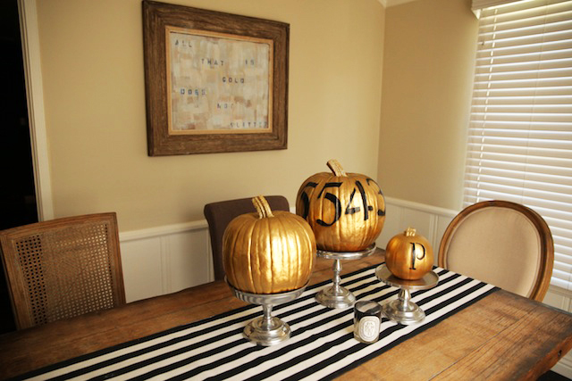 3 gold decorated pumpkins on a table