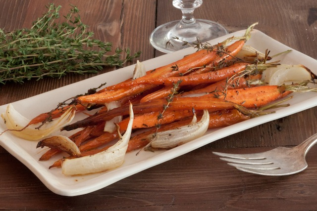 Side dish of roasted carrots on a white plate