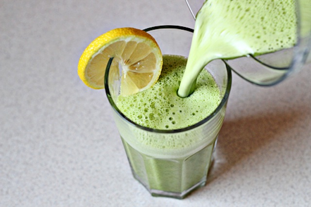 A green smoothie being poured into a glass