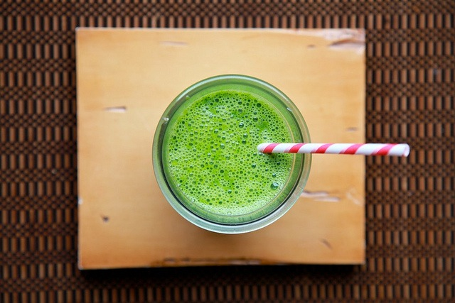 Top shot of a green juice in a glass with a straw