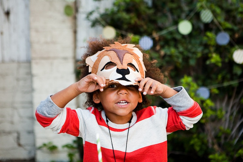 A child in a lion animal mask