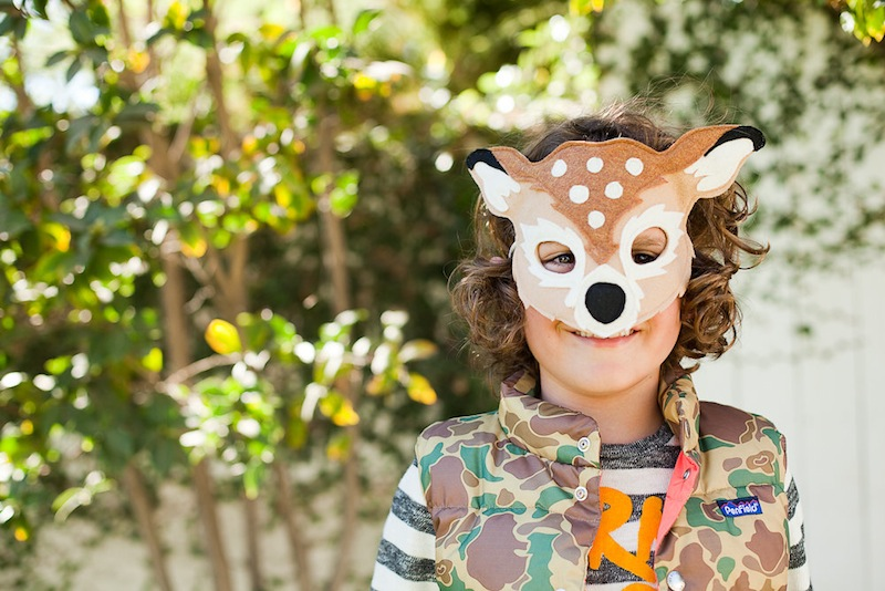 A boy in a deer mask looking at camera