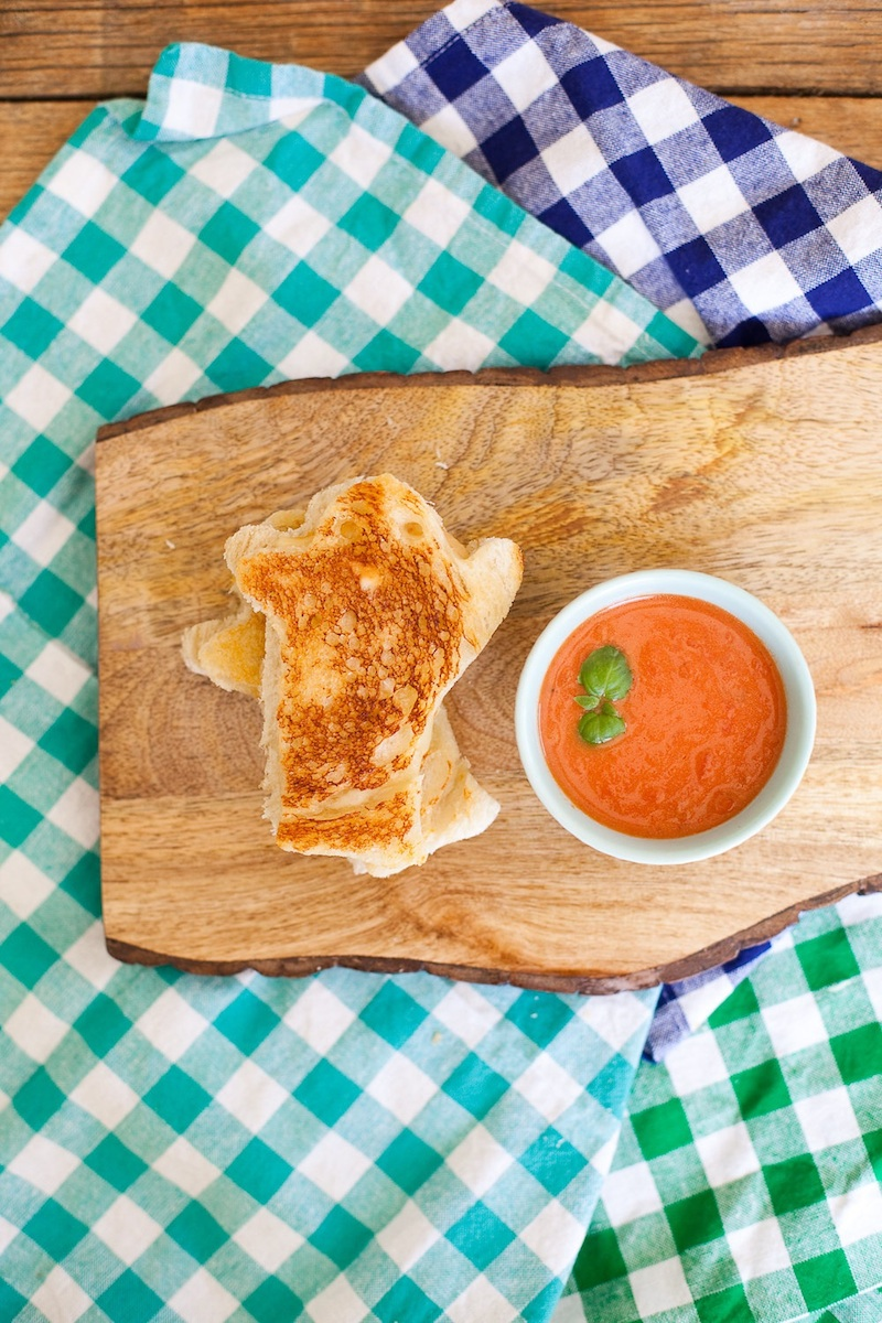 A Grilled Cheese and Tomato Soup on a wooden board