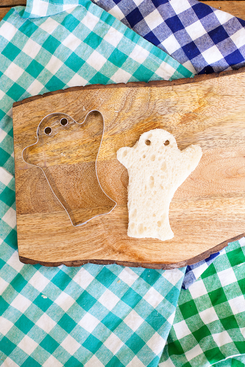 A slice of bread cut out into a ghost shape on a board