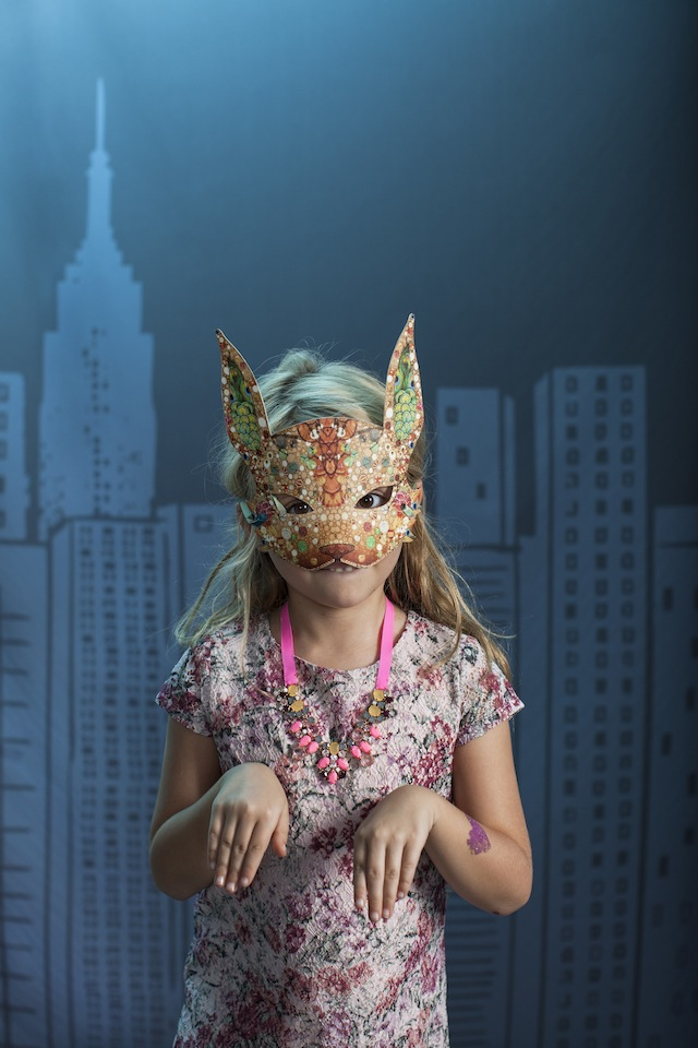 A girl in a colorful animal mask
