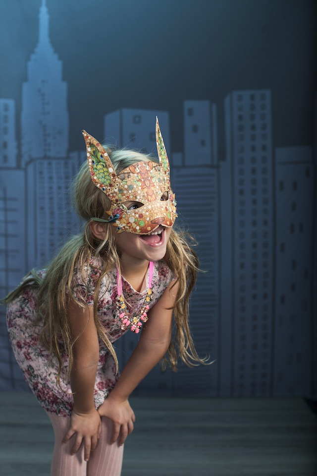 A girl wearing a colorful rabbit mask