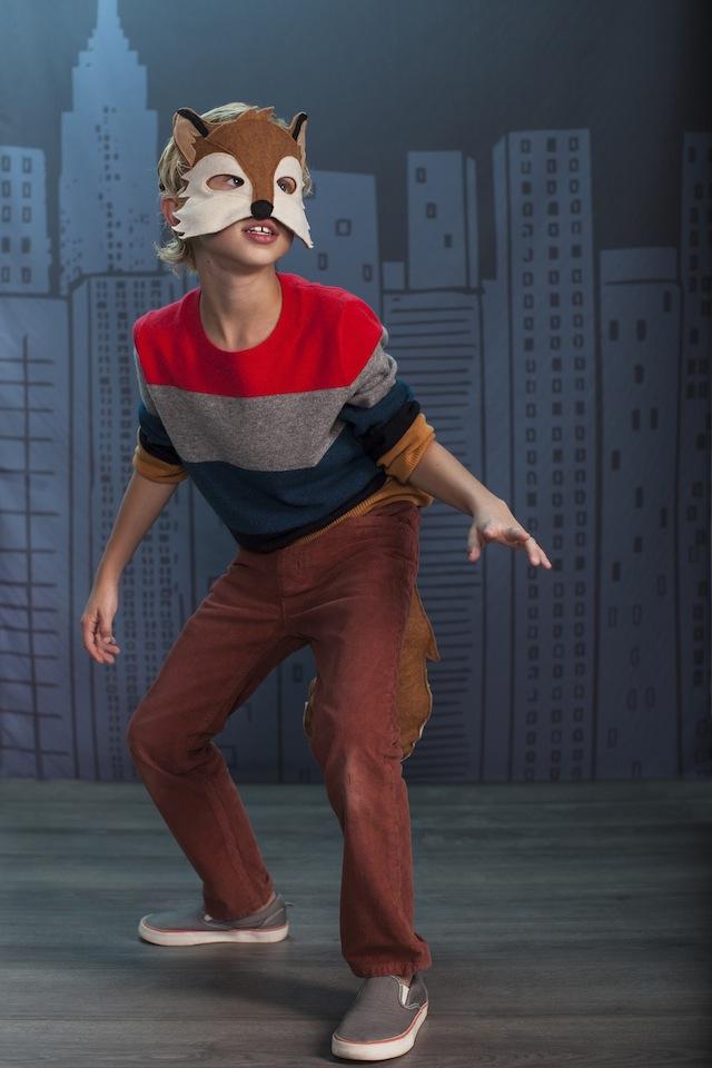 A boy wearing a fox animal mask