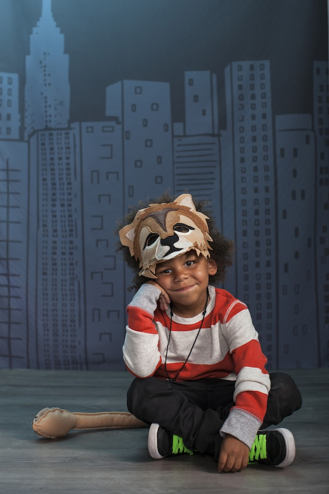 A boy sitting on the floor wearing a lion animal mask