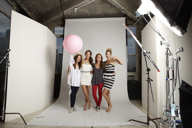 Four people standing in a photography studio