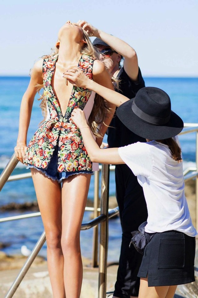 Two people styling a model for a shoot