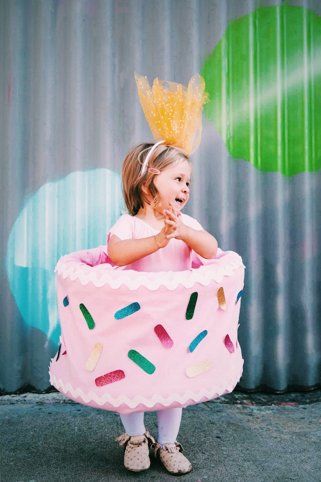 A little girl in a birthday cake costume
