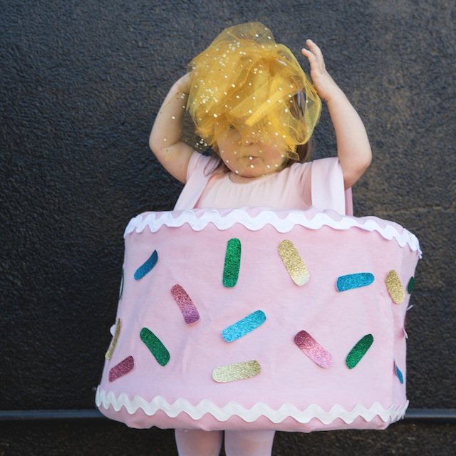 A girl in a birthday cake costume with head piece