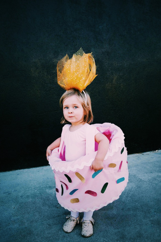 A toddler in a birthday cake costume