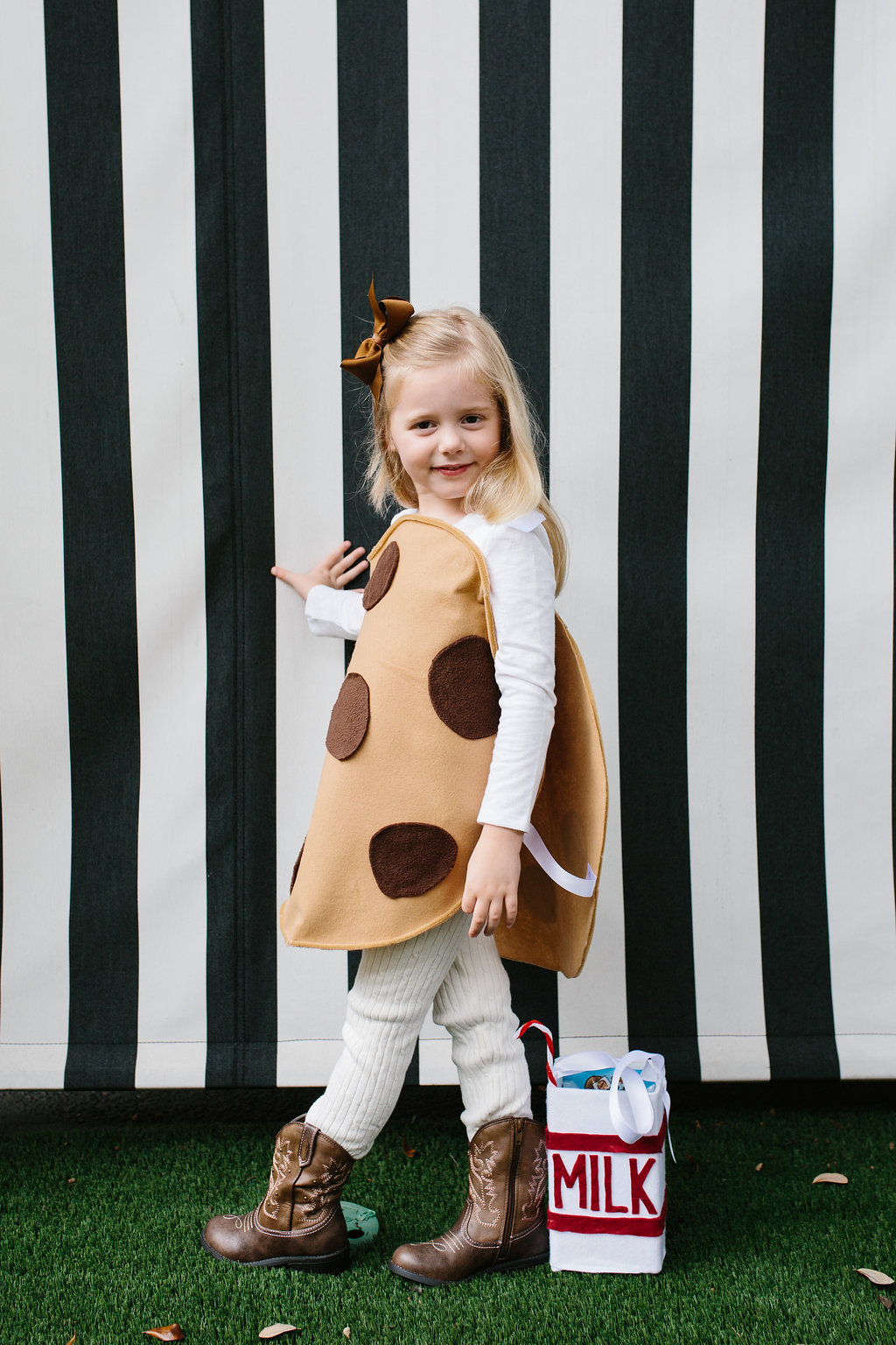 A little girl in a Chocolate Chip Cookie Costume with a carton of milk