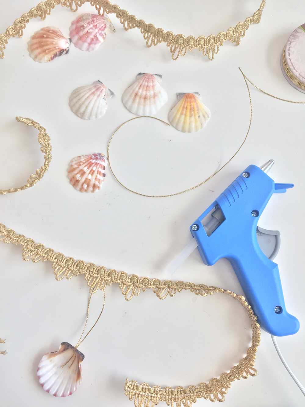A glue gun and shells to make the necklace