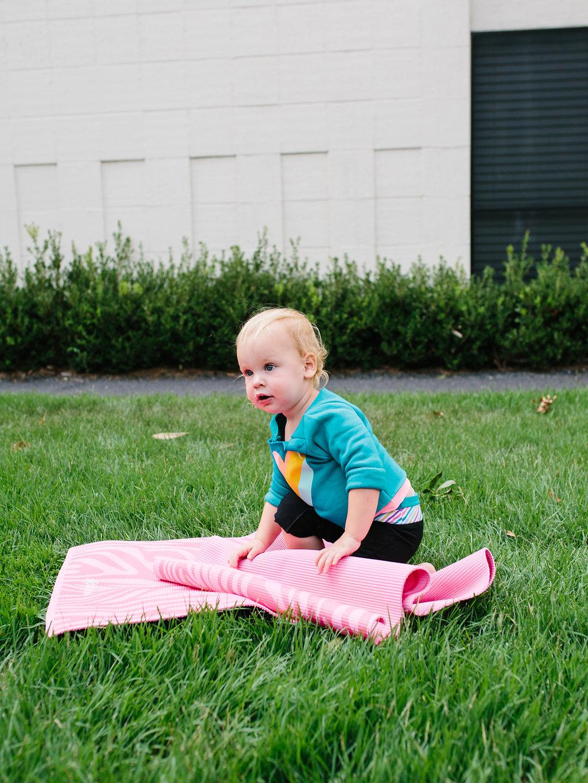 A toddler yogi rolling a mat