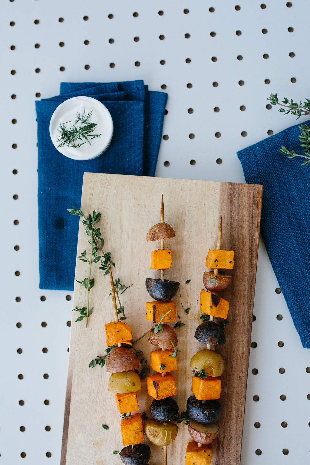 Three vegetable skewers on a wooden chopping board