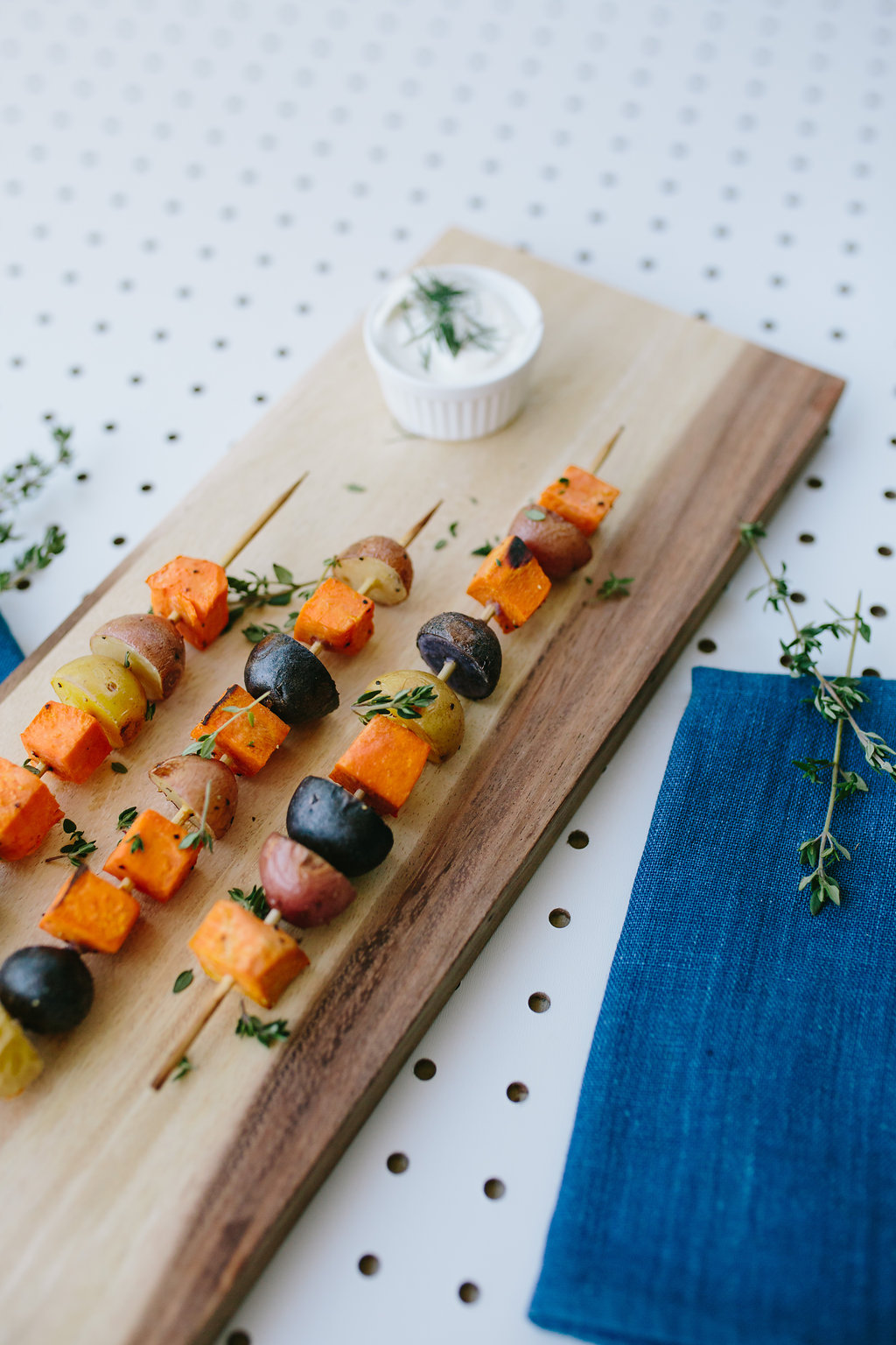 vegetable skewers served on a board with dip