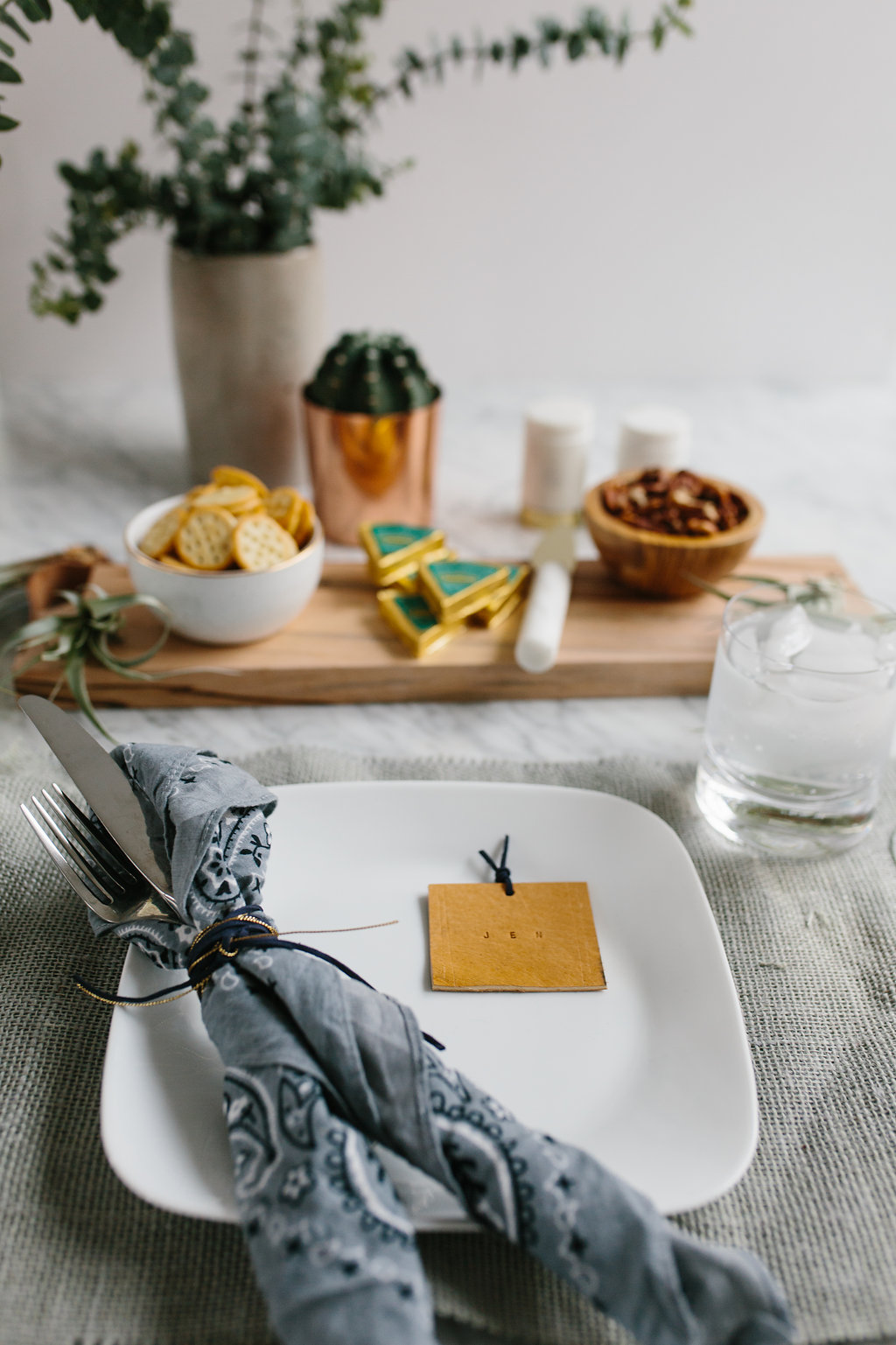 A DIY leather place cards  on a plate next to a knife and fork