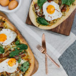 two breakfast pizzas on table with cutlery