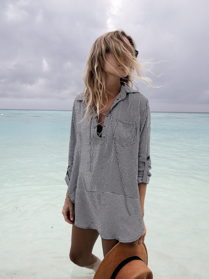 Model in a cover up shirt on the beach