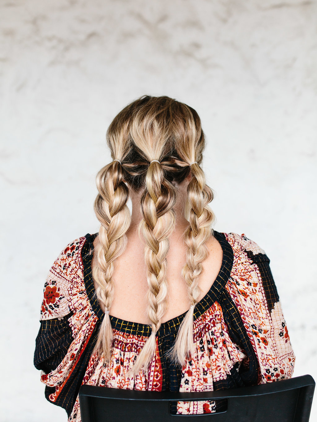 Three braids tied at the back of the head