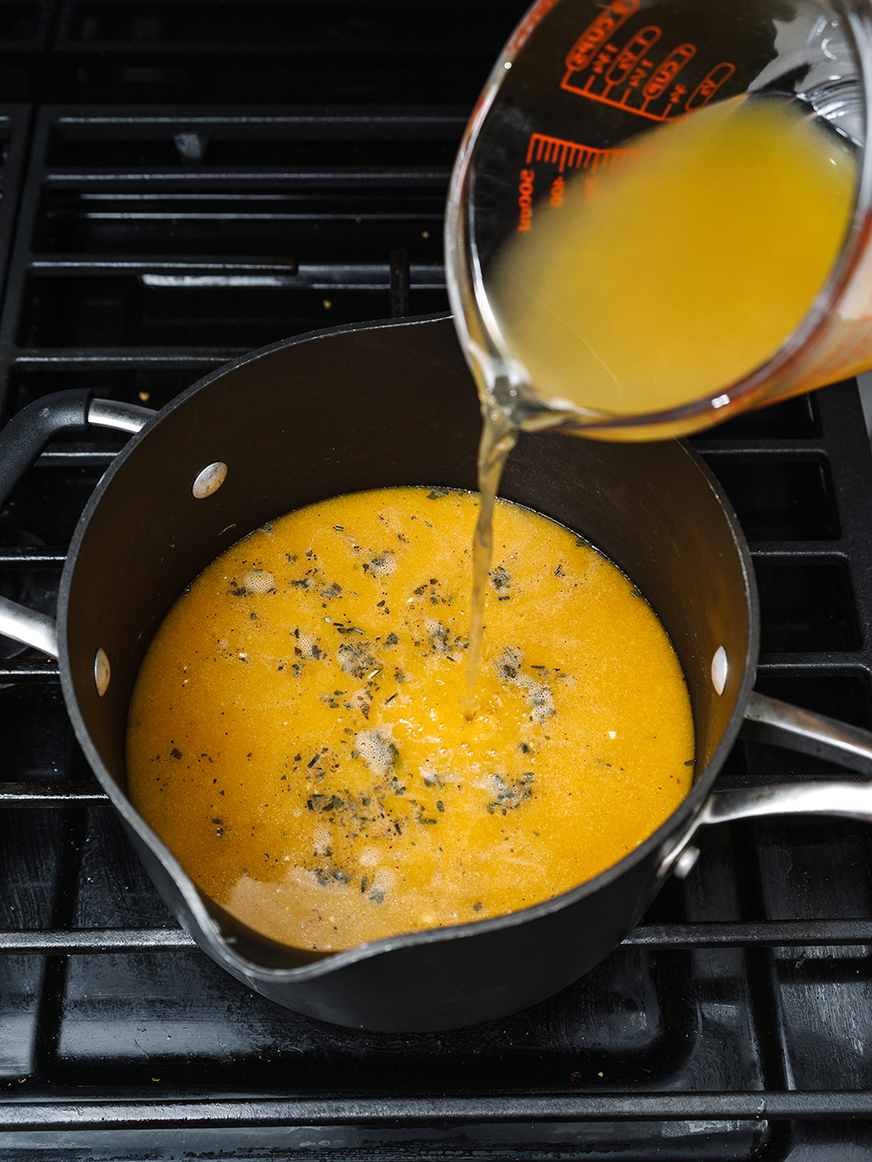 Stock being poured into a pan on the stovetop