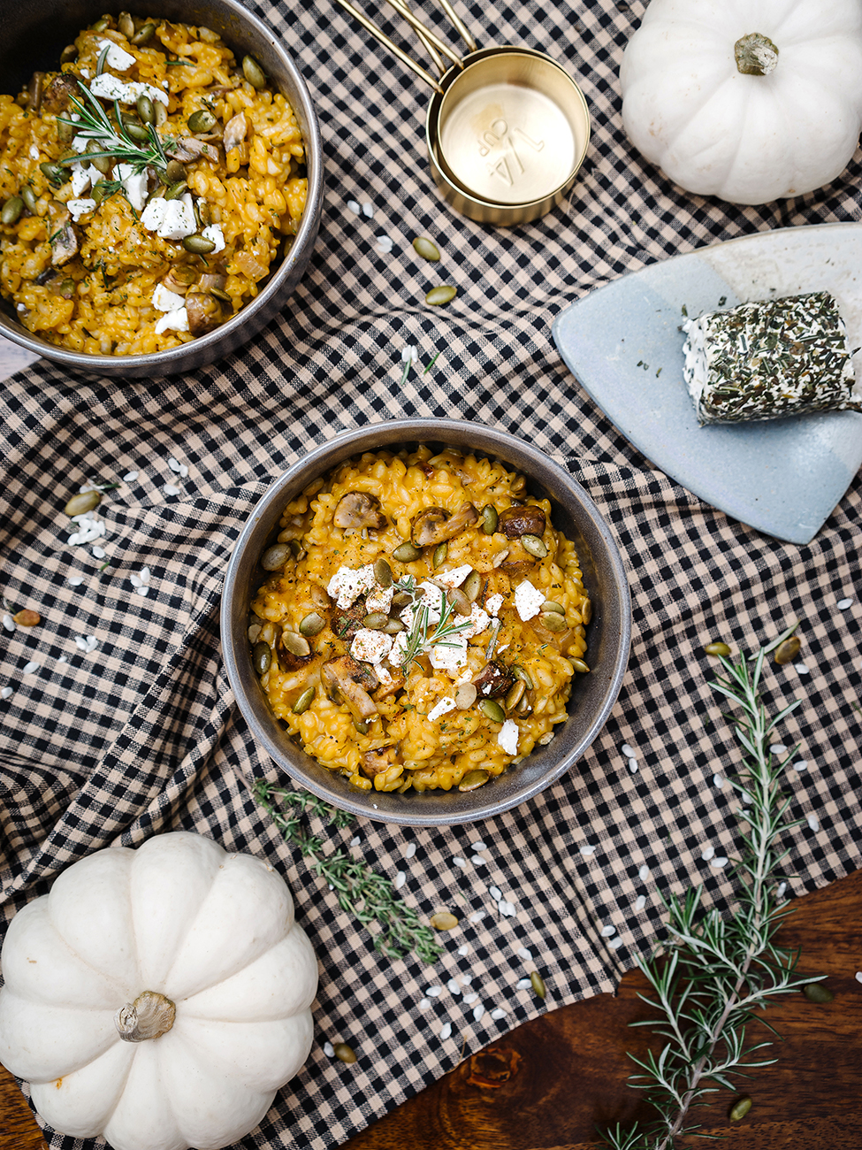 Two bowls of pumpkin risotto on a gingham tablecloth