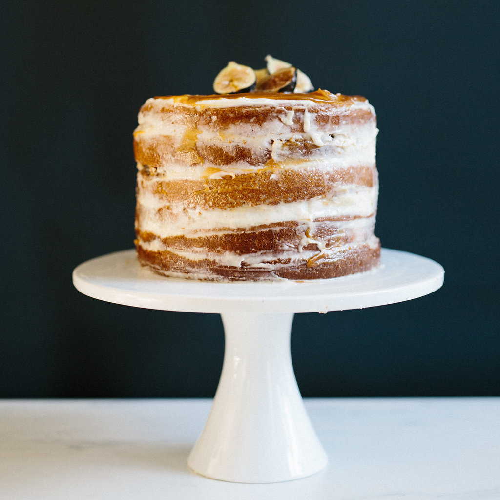 Close up of a pumpkin spiced naked layer cake on a stand