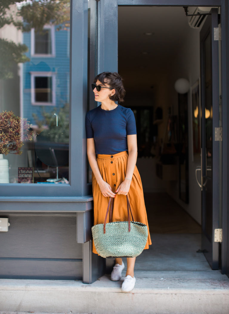 A model wearing an orange midi skirt with blue top