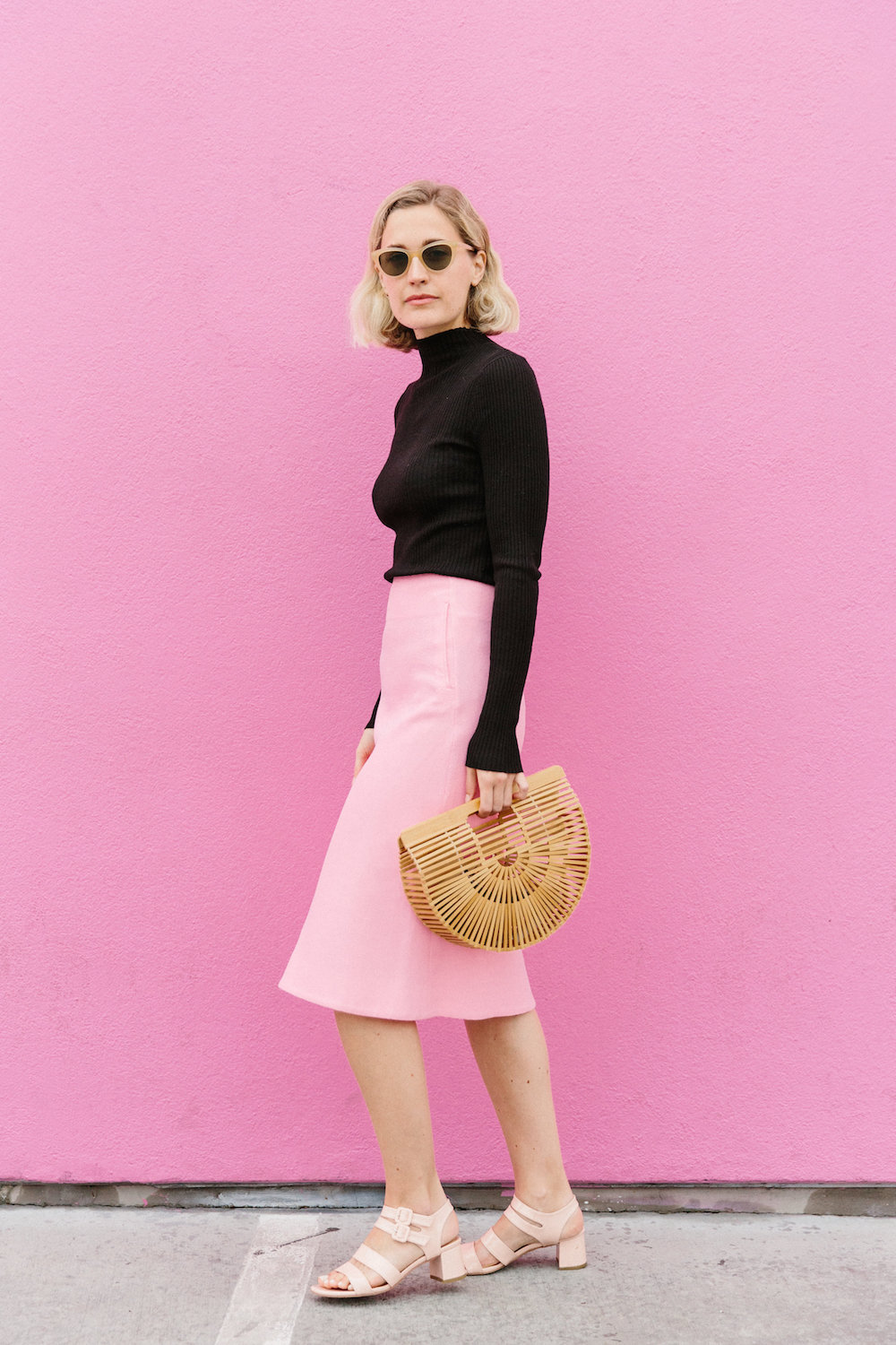 A model against a pink wall wearing a pink midi skirt