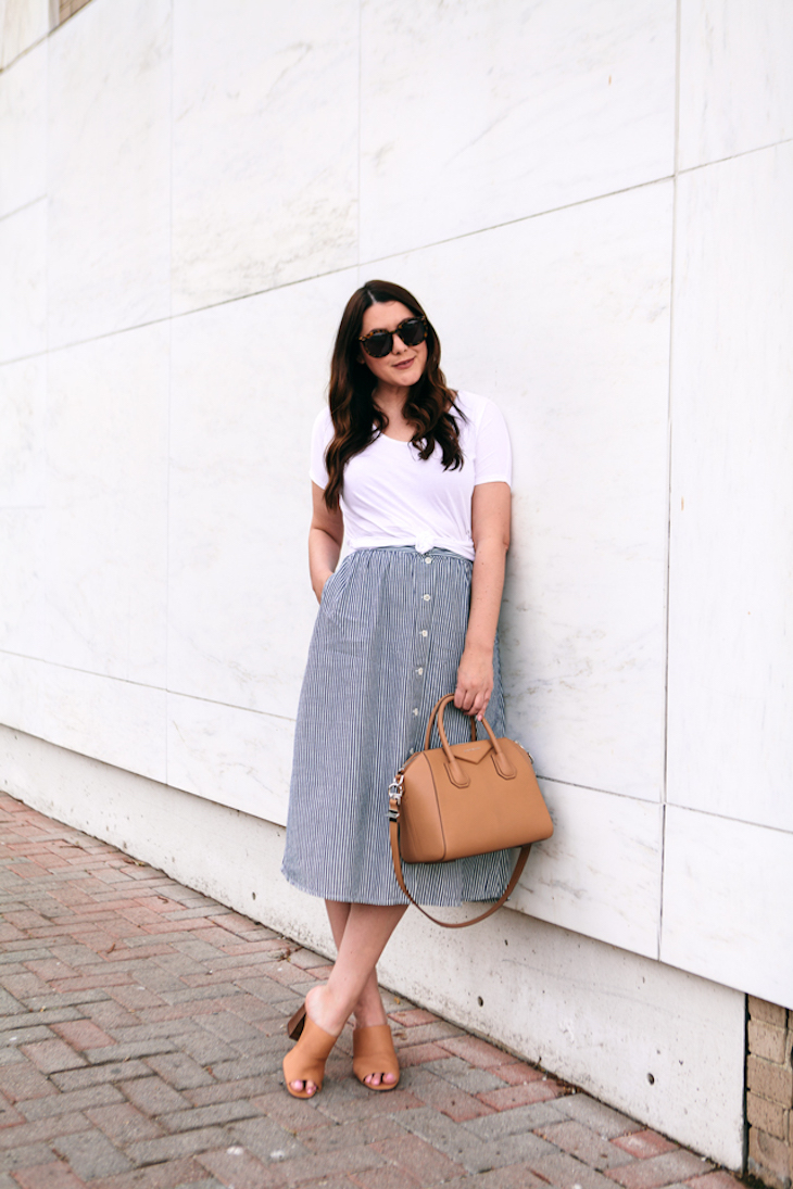 A model in a striped skirt and white top