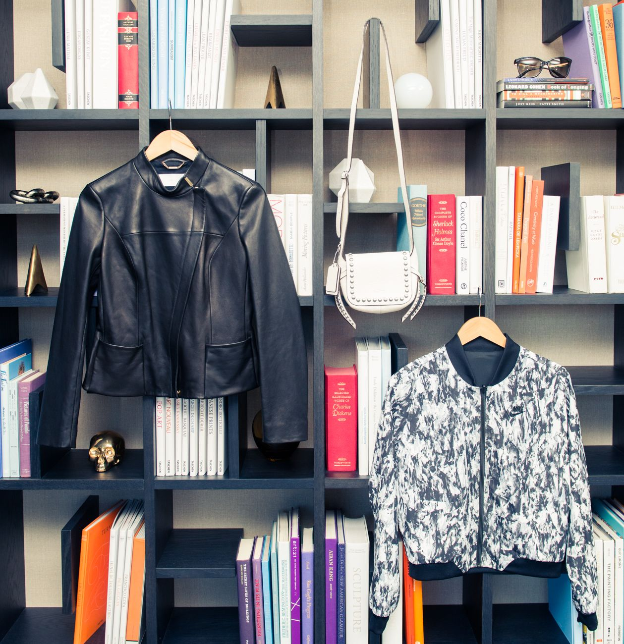 Two jackets hanging on a book shelf