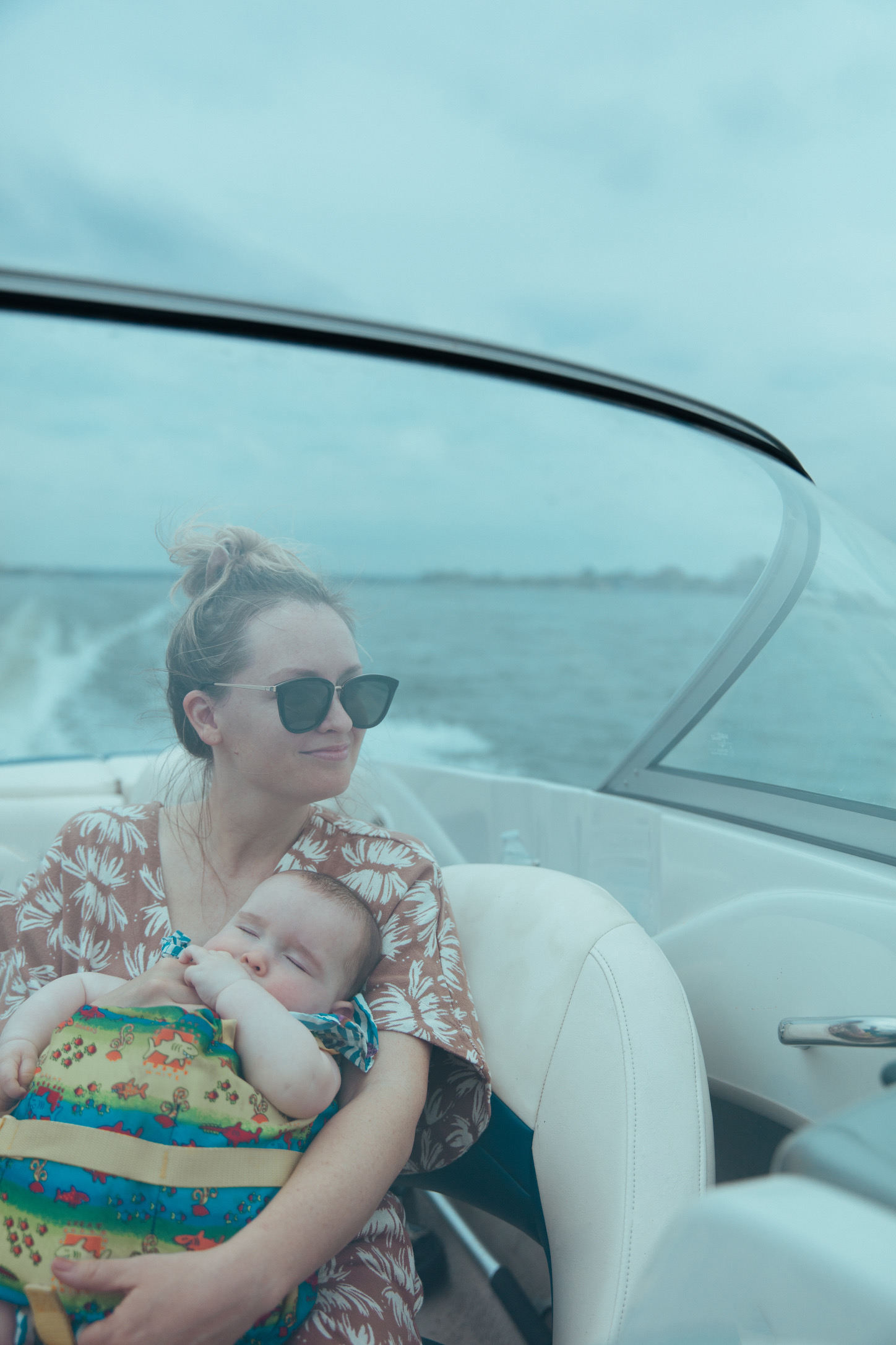 Jen on a boat holding her baby