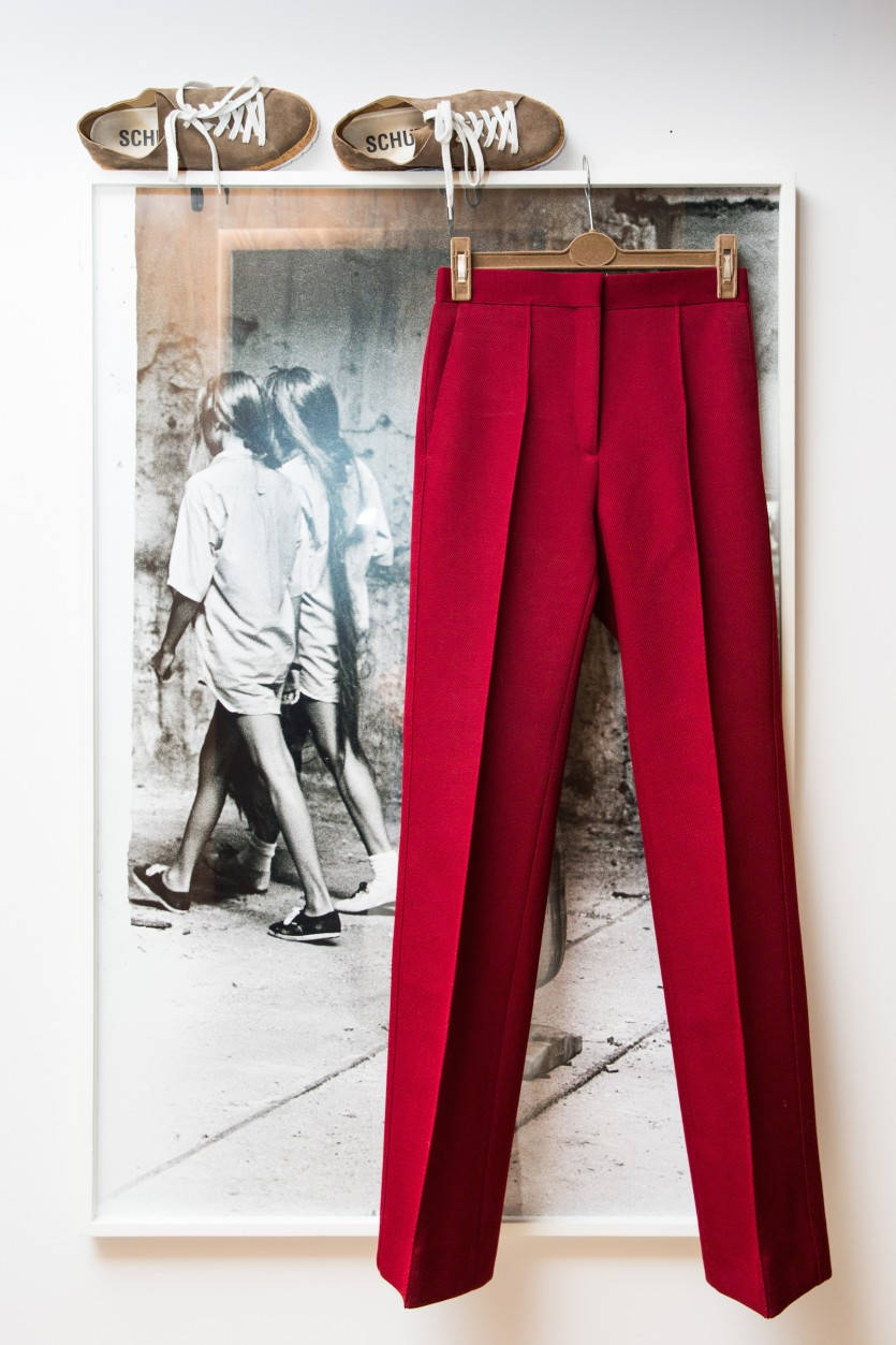 A pair of red trousers hanging on a picture frame