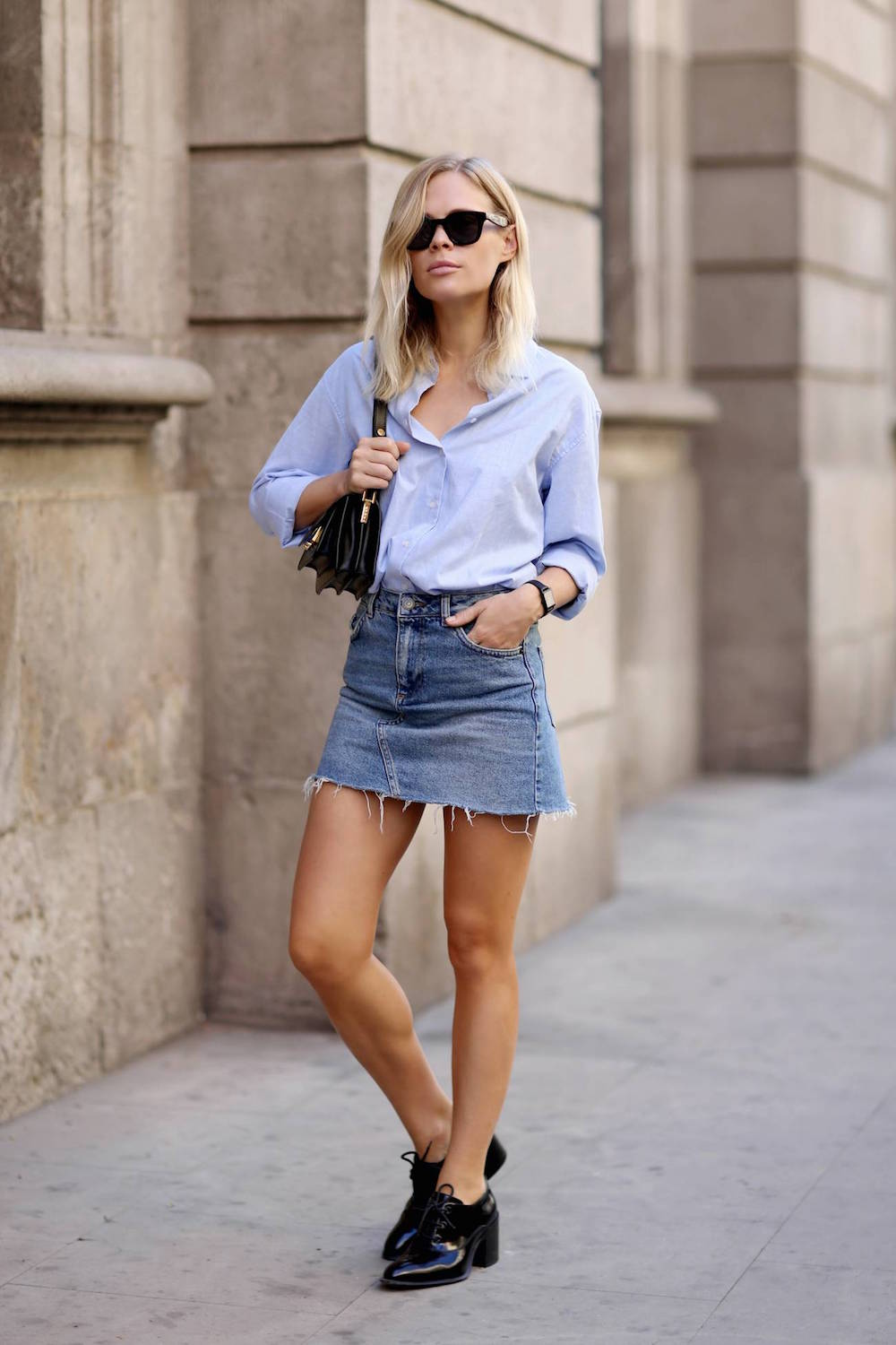 model in a mini denim skirt and blue shirt