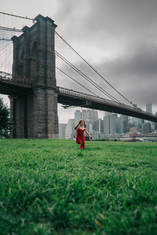 Child running by the Brooklyn Bridge in new york city