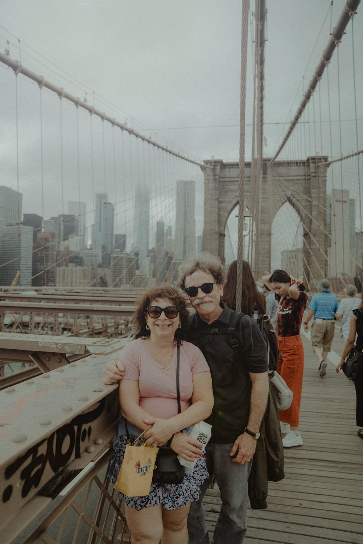 A couple standing on Brooklyn Bridge