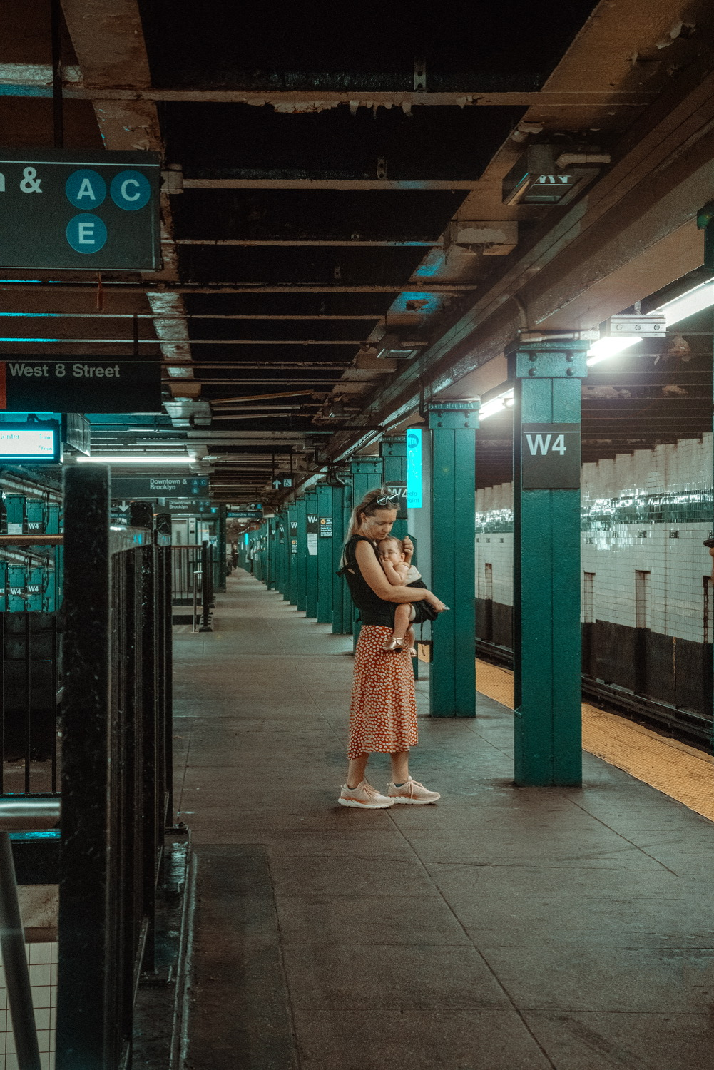 Woman holding a baby on a subway platform