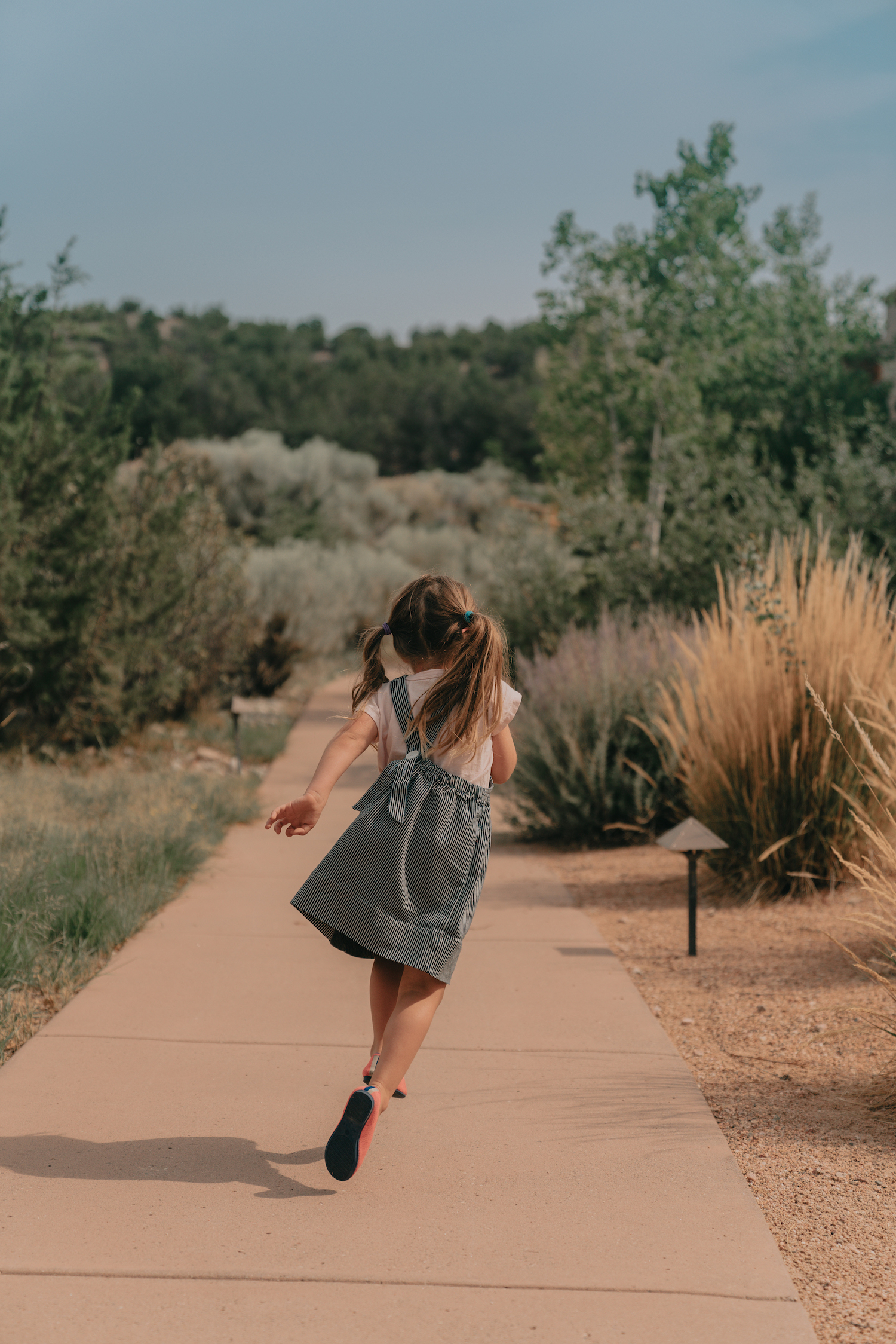 A little girl running along a path