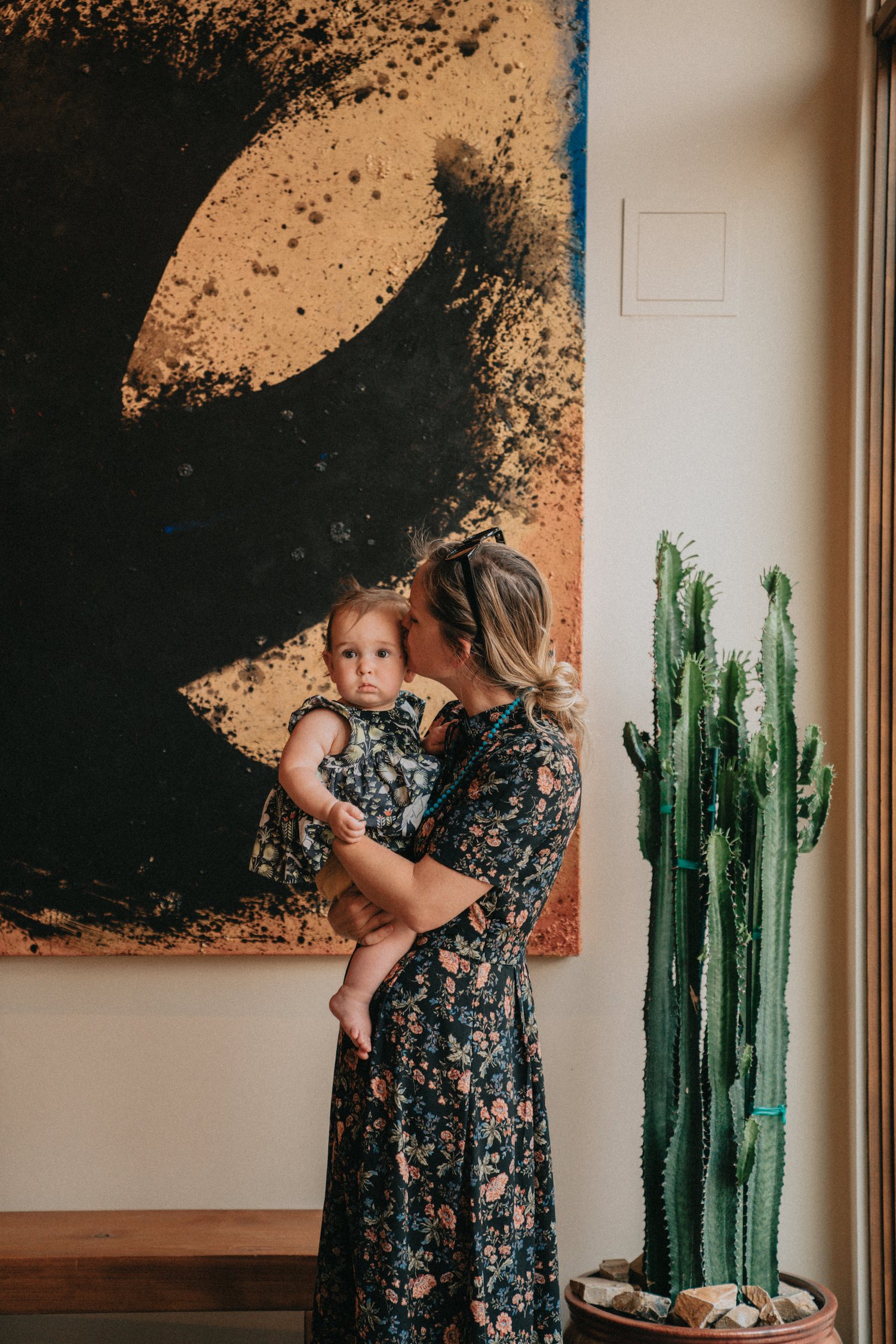 A woman holding a baby in front of a piece of art