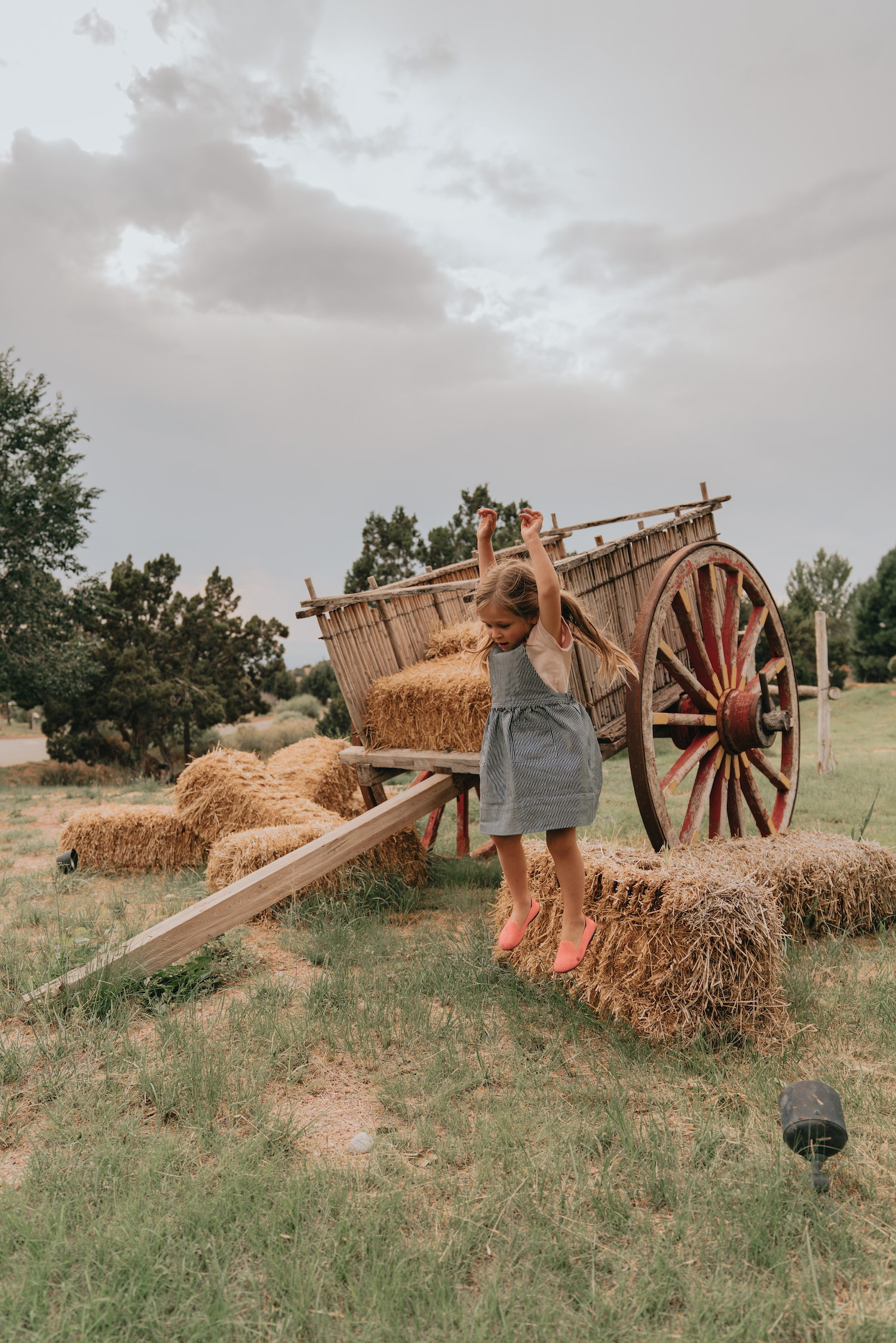 A girl next to an old hay cart