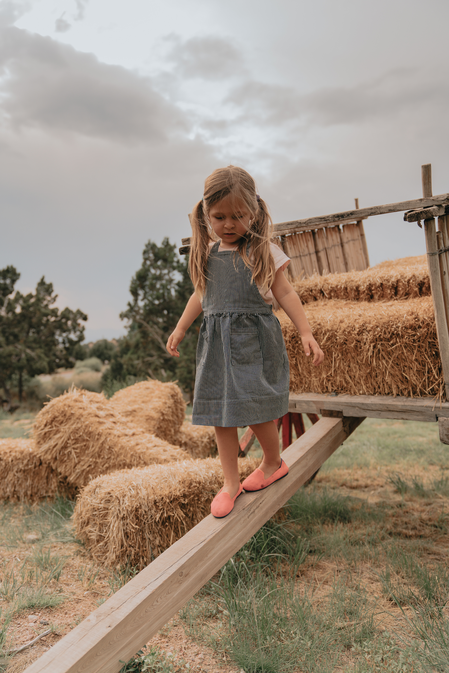 A girl balancing on a hay cart
