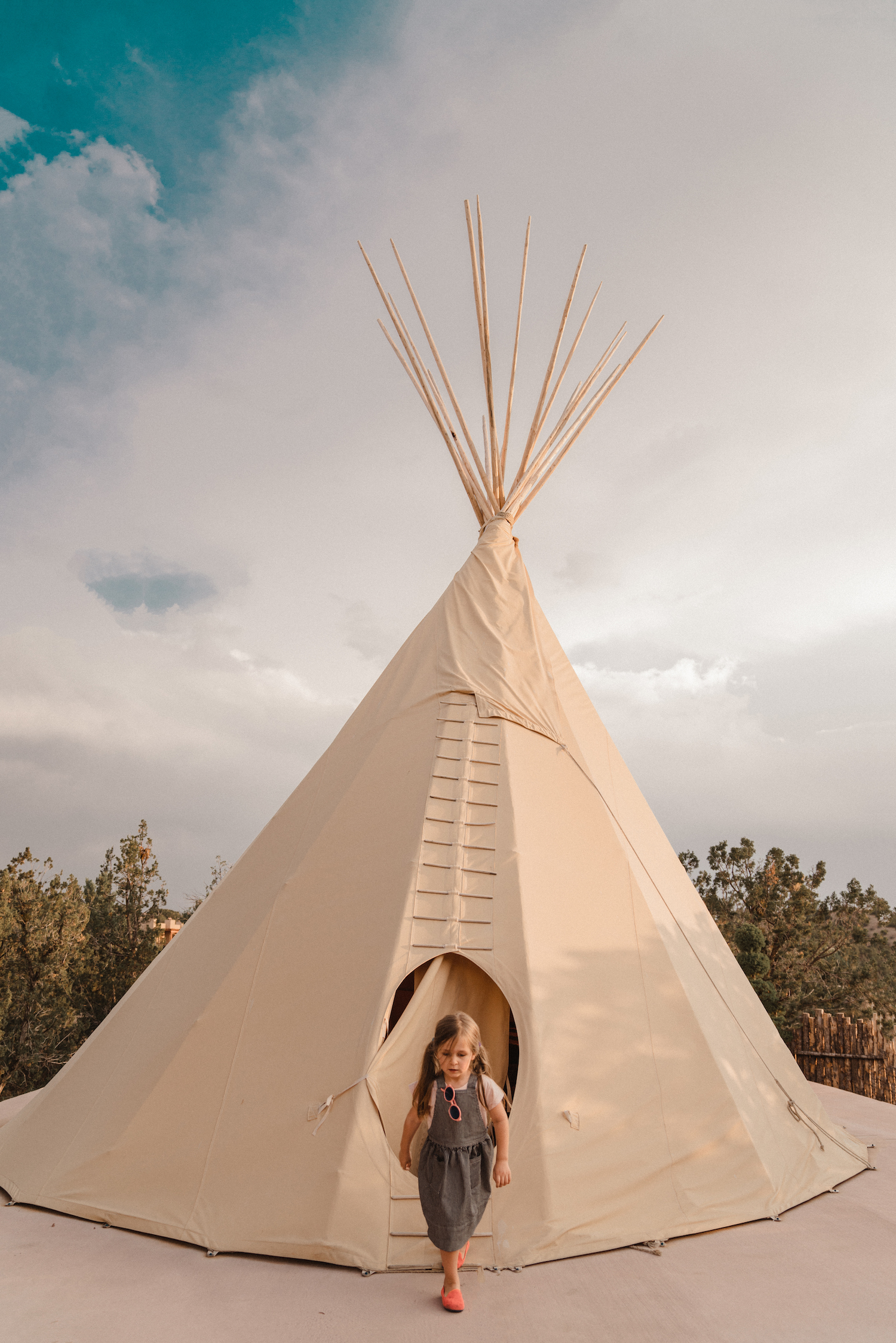 A girl next to a teepee