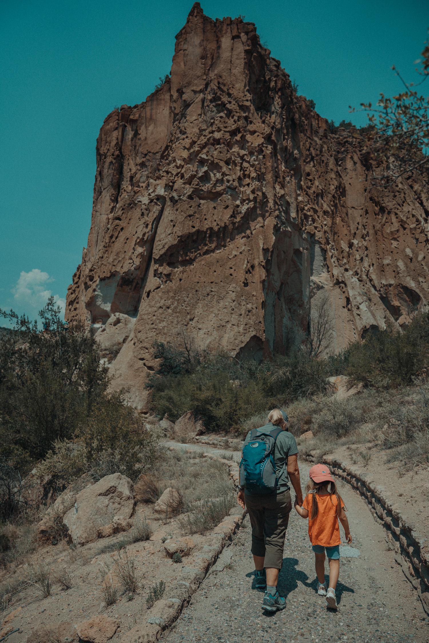 Two people walking towards a Santa Fe rock