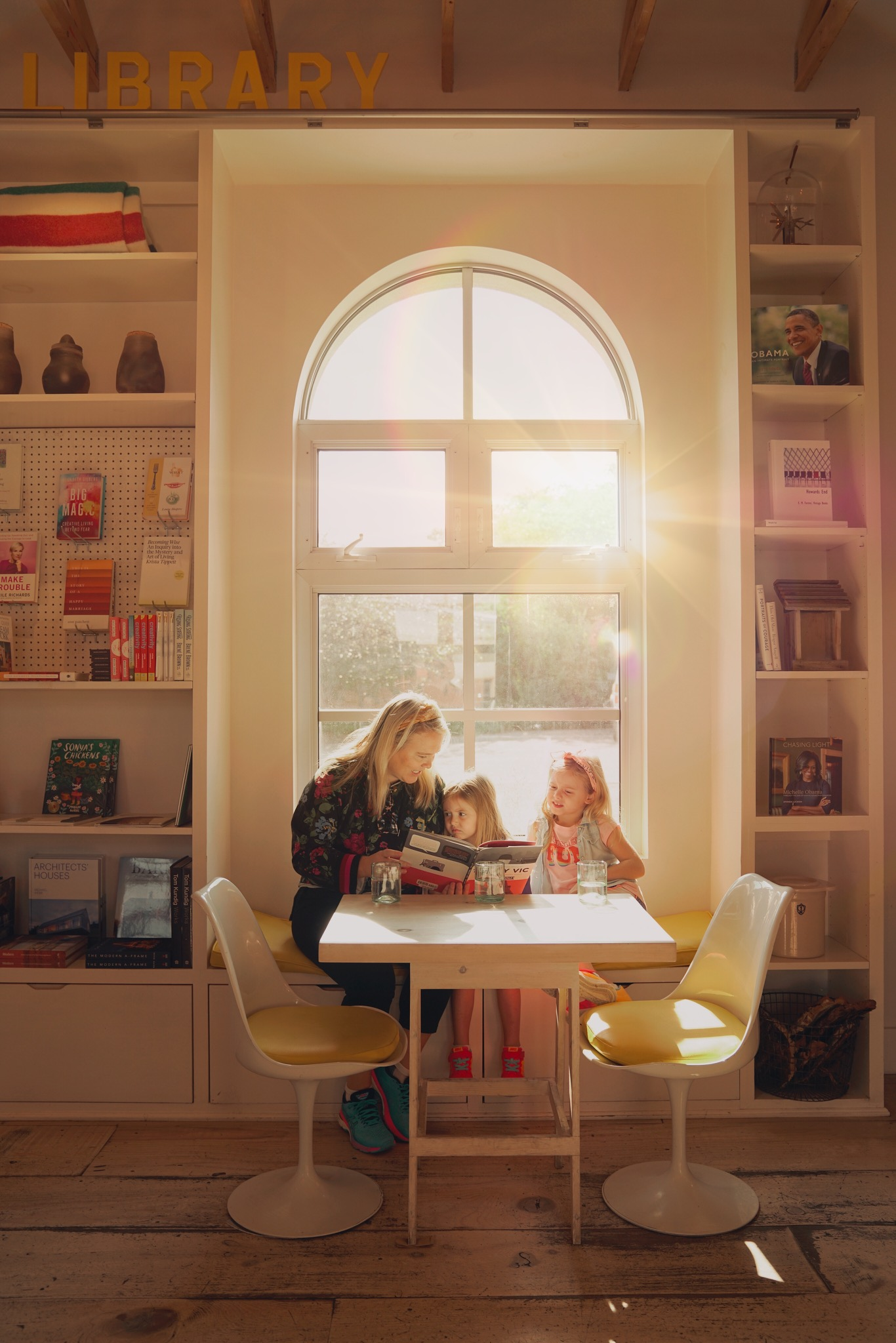 Two children and a woman reading a book