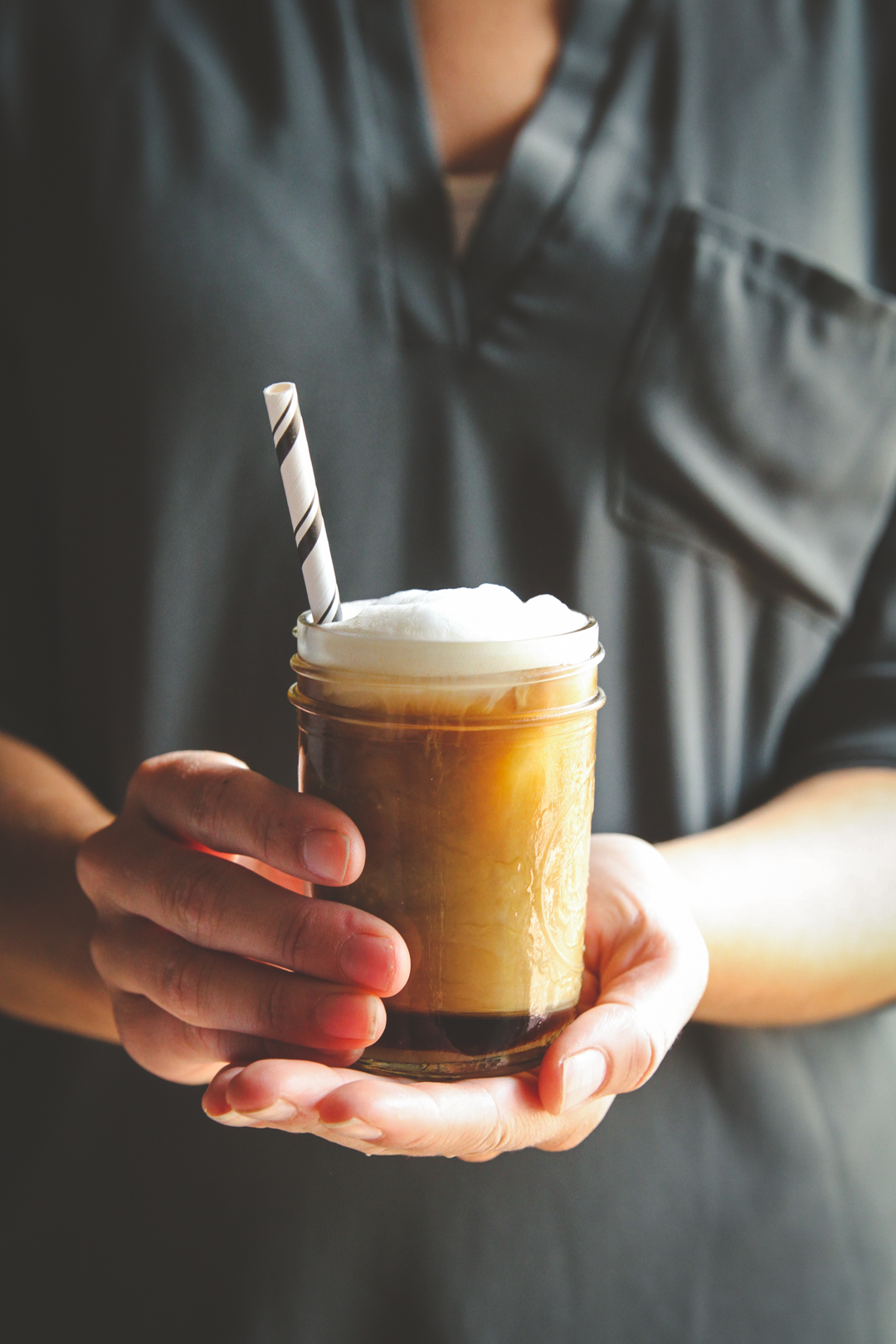 Coffee in a mason jar being held towards camera