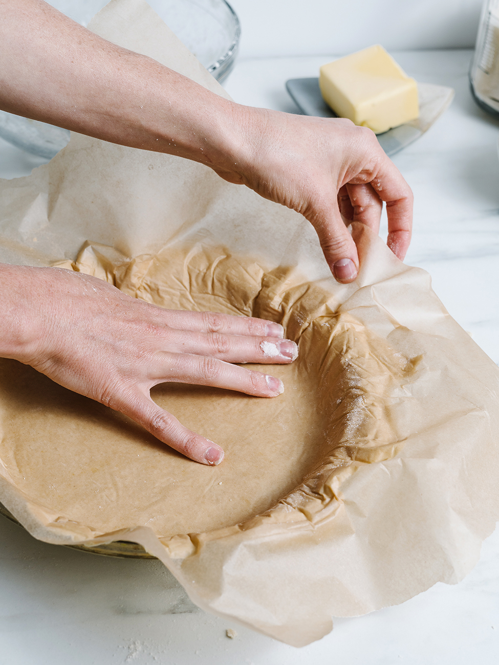 Dough being pressed into a pie tin with parchment