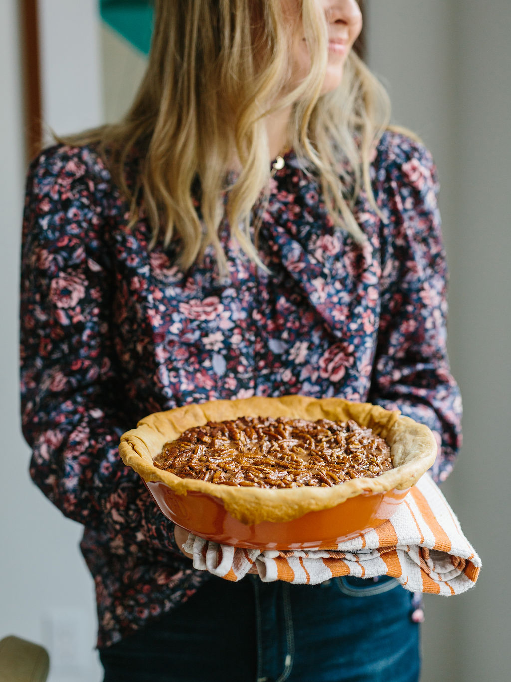 A baked bourbon and chocolate pecan pie being held in a pie dish
